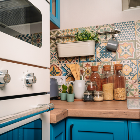 colorful backsplash tiling on top of bright blue cabinets with natural wood countertops