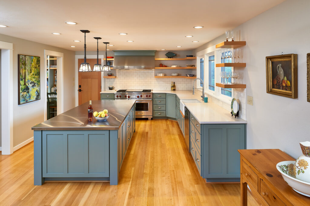 rustic modern kitchen with blue gray cabinets that highlight one of our three key interior design trends in 2021, open shelving and lots of counterspace. Island has stainless steel countertop and flooring is a natural light hardwood