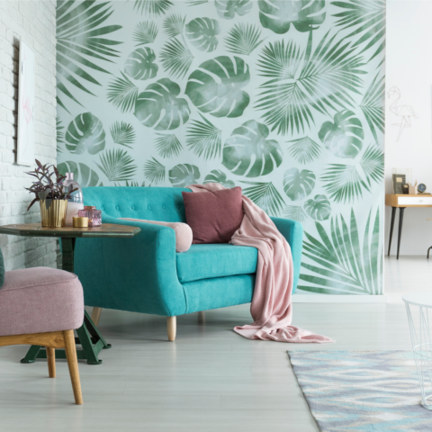 tropical wallpaper accent wall next to white painted brick walls with blue mid-century modern furniture in the foreground