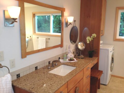 Accessible bathroom vanity using universal design. Brown speckled countertop with large vanity mirror and dual combination washer and dryer. In mirror's reflection is a window wheelchair accessible bath tub.