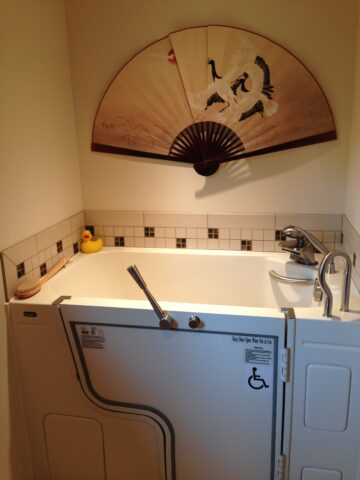 Wheelchair accessible bath tub created with universal design. Yellow rubber ducky in the corner of tub and Asian hand fan artwork on the wall.