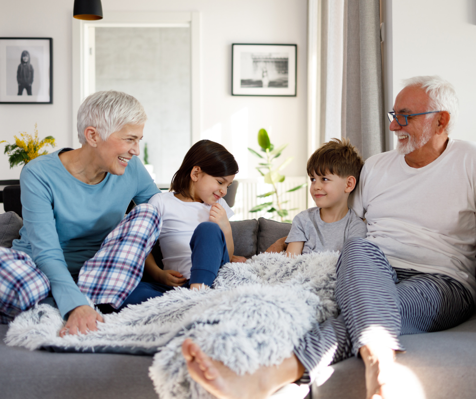 grandparents on the couch with grandchildren laughing multigenerational housing