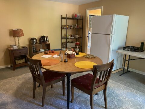 what to expect during construction involves a temporary make shift kitchen located in a spare bedroom with dining room table, fridge, shelves with spices and food and a table with propane cooktop